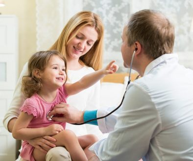 Male Pediatrician examining cute little girl with stethoscope. K